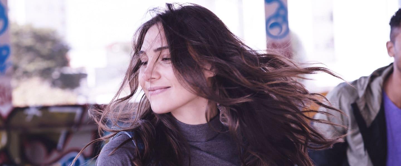 Chica sonriendo con vento en el pello