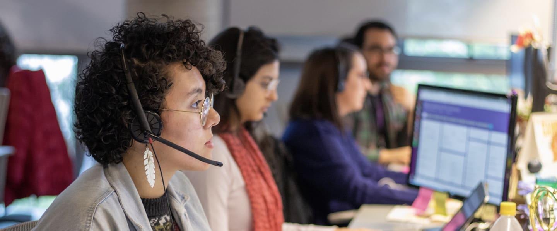 Chicas de la equipo de atención Nu en la computadora con audífonos