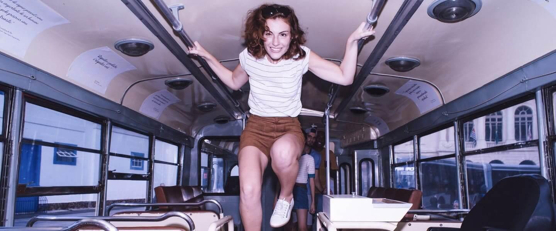 Chica salta sobre la carraca en un autobús
