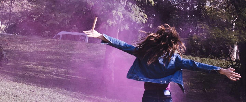 Chica corre con los brazos abiertos en dirección a una nube de humo morada