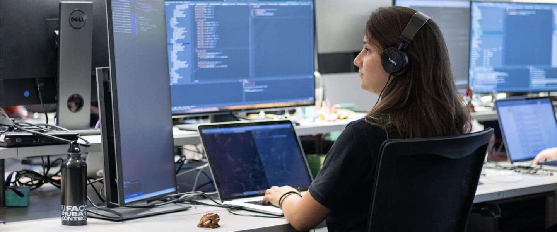 Chica con audífonos escribe en la computadora