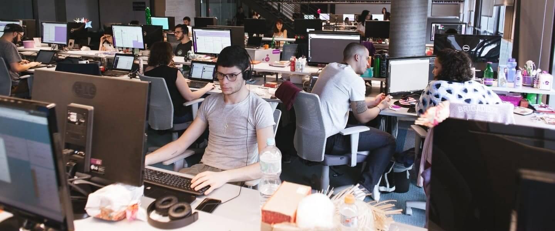 Varias personas trabajando desde sus escritorios, en un ambiente de trabajo diverso, libre y ameno.