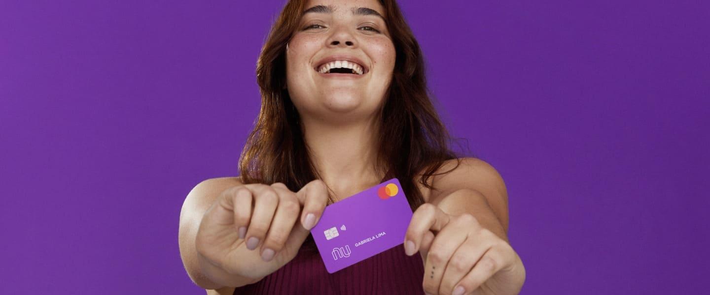 Mujer adolescente sostiene la tarjeta de crédito Nu, mientras ríe al acordarse que no tiene anualidad ni comisiones.