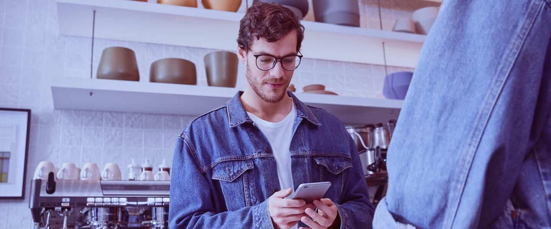 Comerciante recibe una notificación de pago a través de la app Nubank en su celular, en tiempo real