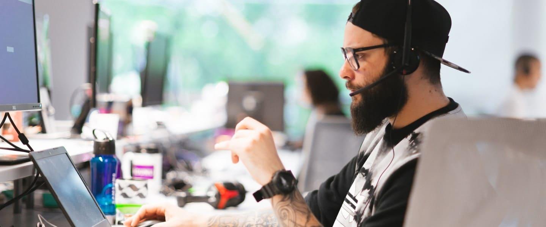 Al ser parte del extraordinario Servicio al Cliente Nu, un hombre con audífonos se encuentra concentrado en resolver una problemática de un cliente.