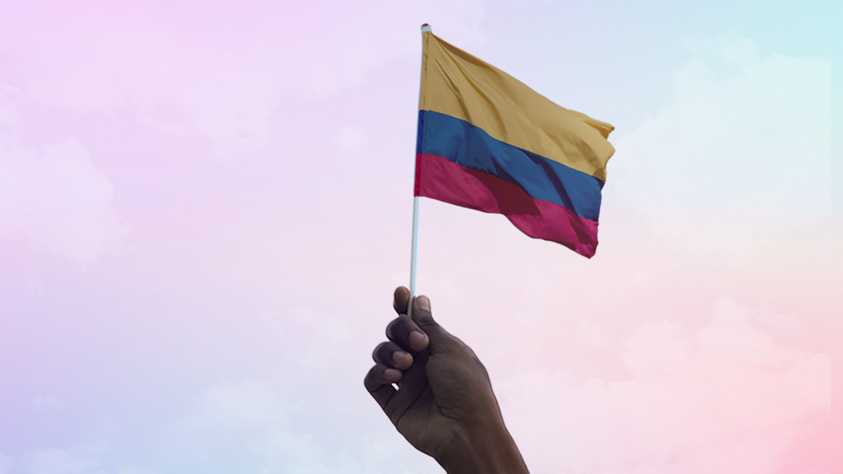 Nubank llega a Colombia: mano sostiene bandera colombiana en el aire